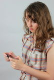Girl checking smart phone. Deepened young woman is checking the news from her smart phone; neutral background Stock Images