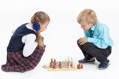 Girl checkmates boy, schoolchildren in uniform playing chess, isolated white background Royalty Free Stock Photos