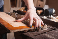 The girl checks the angle,. The carpenter works in a workshop Royalty Free Stock Image