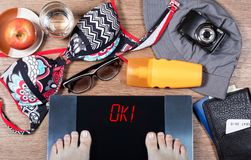 Girl checks her body weight before summer vacation. Word ok! on digital scales. Concept of healthy lifestyle. And being in good form for vacation. Top view Royalty Free Stock Image