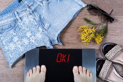 Girl checks her weight on digital scales before going for a walk. Concept of being in form before spring. Sign ok! on weighing machine surrounded by mimosa Stock Image