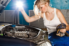 Girl checks the oil level in the car. Girl checks the oil level with dipstick in their own broken car Royalty Free Stock Images