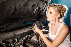 Girl checks the oil level in the car. Girl checks the oil level with dipstick in their own broken car Royalty Free Stock Photography