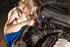 Girl checks the oil level in the car. Girl checks the oil level with dipstick in their own broken car Royalty Free Stock Image