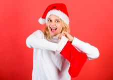 Girl cheerful face check out gift in christmas sock. Woman in santa hat unpacking christmas gift red background. Check. Contents of christmas stocking what she royalty free stock photos