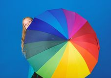 Girl cheerful hide behind umbrella. Colorful umbrella accessory. Weather forecast concept. Stay positive though rainy stock photo