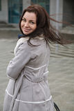 Girl with a cheerfull smile on the street. Portrait of a stylish beautiful girl on the street in grey coat Stock Photo