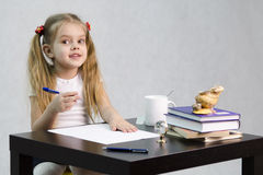 The girl happily looks in the frame, sitting at the table in the image of the writer Stock Photos