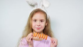 The girl cheerfully nibbles carrot pieces on a stick. Child with bunny ears eating carrot.  stock video