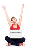 Girl cheering with laptop. Girl with laptop raising her arms in joy Royalty Free Stock Photo