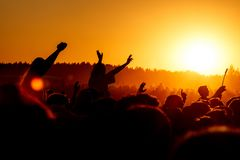 Girl cheering at outdoor music, rock festival. Man with raised hands cheering at outdoor music, rock festival royalty free stock photography