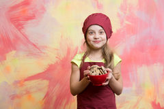 Girl chef or child cook in hat with cookie food. On colorful background, copy space Royalty Free Stock Photography