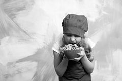 Girl chef or child cook in hat eating cookie food. Child cook or girl chef in hat eating cookie food on colorful background, copy space Stock Photo