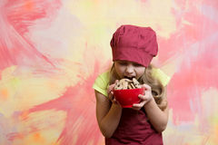 Girl chef or child cook in hat eating cookie food Royalty Free Stock Image