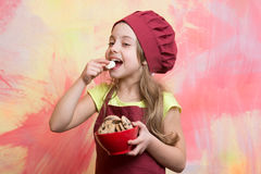 Girl chef or child cook in hat eating cookie food Stock Photography