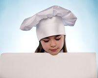 The girl with chef hat indicates  with billboards Royalty Free Stock Photography