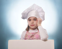 The girl with chef hat indicates  with billboards Stock Photography