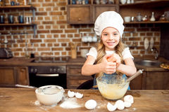 Girl in chef hat making dough for cookies Stock Photos