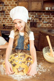 Girl in chef hat making shaped cookies in kitchen Stock Images