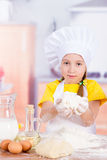 Girl chef holding a pile of flour, eggs Stock Images