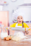 Girl chef holding a rolling pin in hand Stock Image