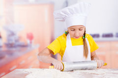Girl chef holding a rolling pin in hand Royalty Free Stock Photography