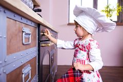Girl in chef`s hat is putting gingerbread cookies in the oven.  royalty free stock photos