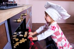 Girl in chef`s hat is putting gingerbread cookies in the oven.  royalty free stock image