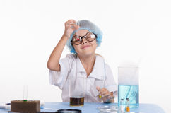 Girl chemist looking at a liquid in test tube Stock Photos
