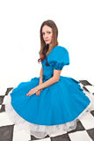 The girl on the chequerboard. The pretty girl in blue dress on the self made chequerboard Stock Photo