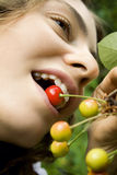 Girl with cherry. Girl is biting cherry in summer Royalty Free Stock Photo