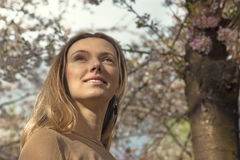 Girl with Cherry Blossom. Beautiful Blonde Young Woman. Royalty Free Stock Photo