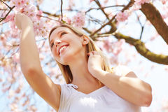 Girl at cherry blossom in a garden Stock Image