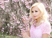 Girl with Cherry Blossom. Spring Flowers. Beautiful Blonde Woman Royalty Free Stock Images