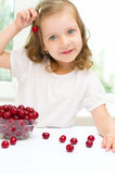 Girl with cherry. Little girl with cherry berries bowl indoors Royalty Free Stock Images