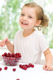Girl with cherry. Little girl with cherry berries bowl indoors Stock Photos
