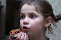 The girl with a cherry-pie. The portrait of a girl in the room Royalty Free Stock Photo
