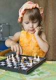 The girl with chess. The girl plays chess figures royalty free stock photography