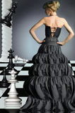 The girl and chess. The glamour girl costs on a chessboard Royalty Free Stock Image