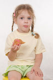 Girl chews thoughtfully bun sitting on a chair Royalty Free Stock Photography