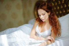 Beautiful sexy redhair lady in elegant white panties and peignoir. Fashion portrait of model indoors. Beauty woman with lace linge Royalty Free Stock Photo