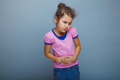 Girl child abdominal pain on a gray background Royalty Free Stock Photo