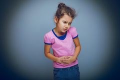 Girl child abdominal pain on gray background cross Stock Photo