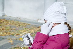Girl child adjusts earphones talk on mobile. Girl child adjusts earphones talk on a cell autumn outdoors Stock Images