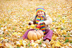 Girl child in autumn forest, sit on yellow leaves, eat apple and pumpkin Royalty Free Stock Image