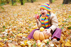 Girl child in autumn forest, sit on yellow leaves, eat apple and pumpkin Royalty Free Stock Images