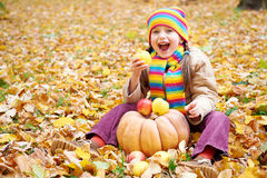 Girl child in autumn forest, sit on yellow leaves, eat apple and pumpkin Royalty Free Stock Photo