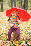 Girl child in autumn forest with umbrella, beautiful landscape in fall season with yellow leaves Royalty Free Stock Photos