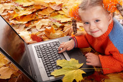 Girl child in autumn orange leaves with laptop. Royalty Free Stock Photography
