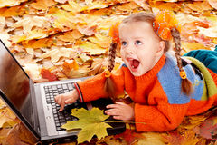 Girl child in autumn orange leaves with laptop. Royalty Free Stock Image